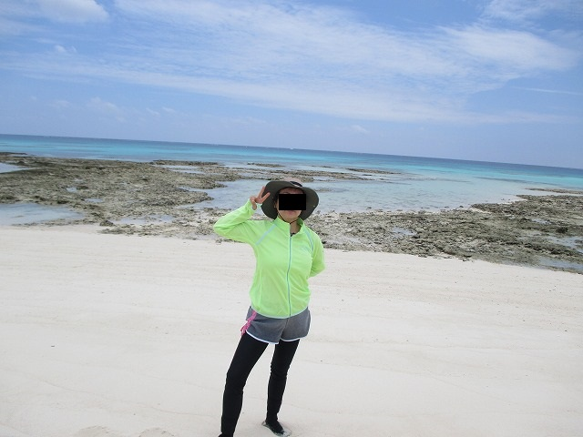 砂浜でピースサインをする女性