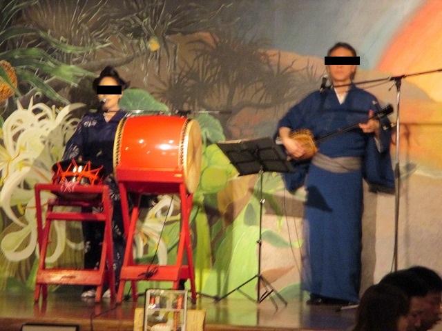 太鼓を叩いている女性と三線を引く男性