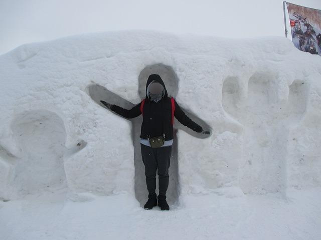 雪でできた人形にはまる女性