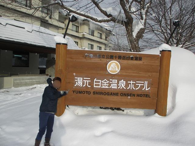 白金温泉ホテルの看板と女性