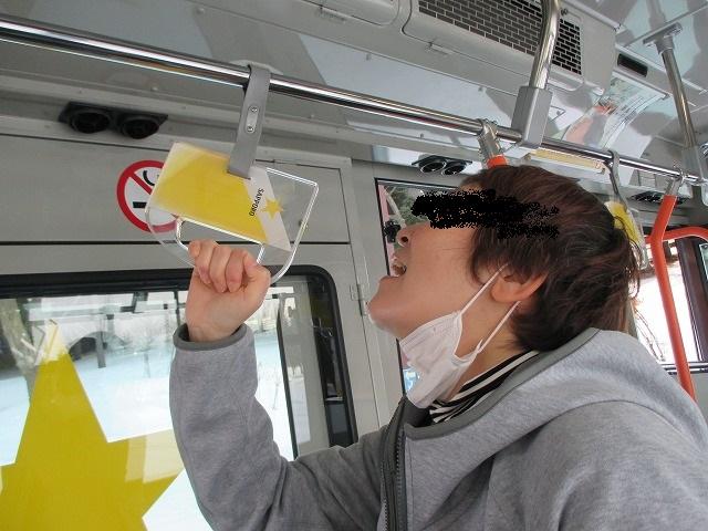 ビールの形のつり革を飲んでいるふりの女性