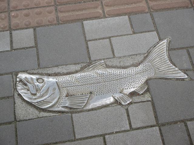 地面に埋め込まれた鮭のオブジェ
