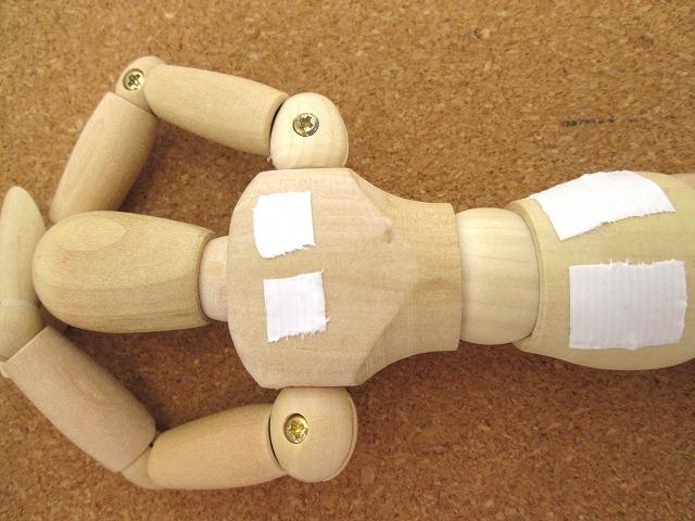 肩と腰に湿布薬を貼っているデッサン人形