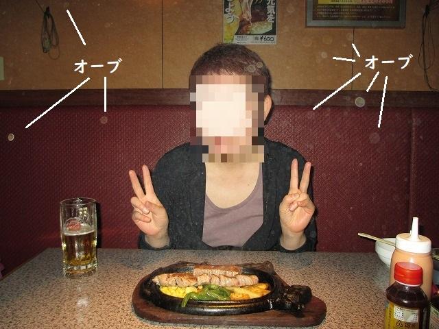 ステーキの前でVサインをする女性