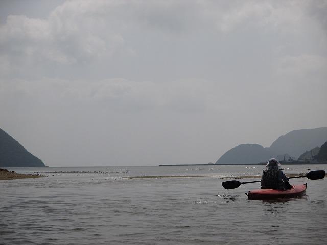海と川の境目に女性の後ろ姿