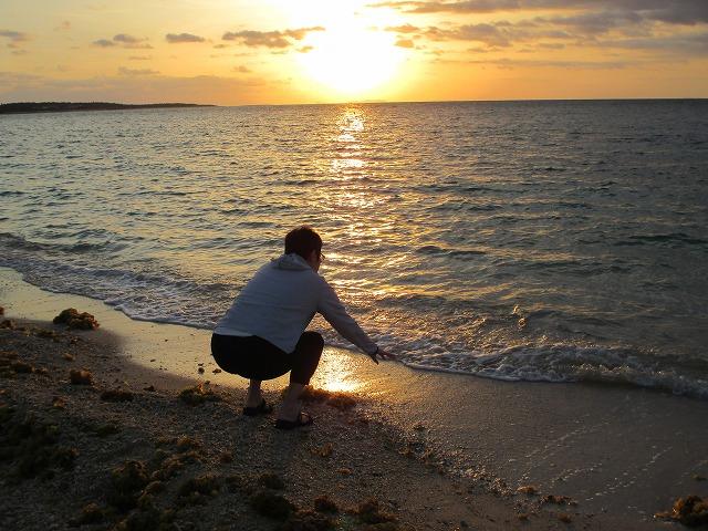 海の水に手をつける女性