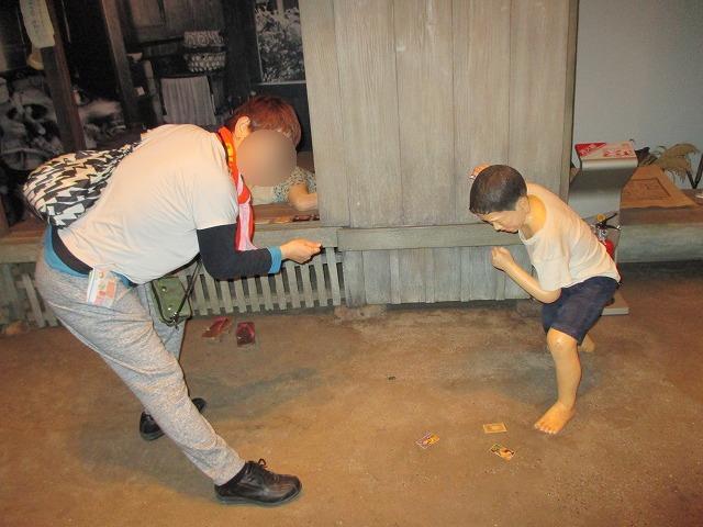 メンコで遊ぶ少年と女性
