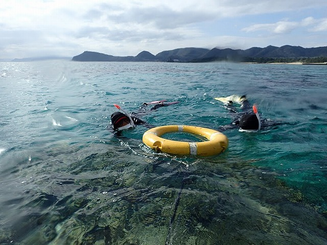 シュノーケルをする女性と浮き輪