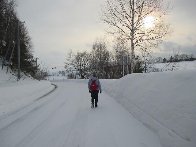 雪道を歩く後ろ姿の女性